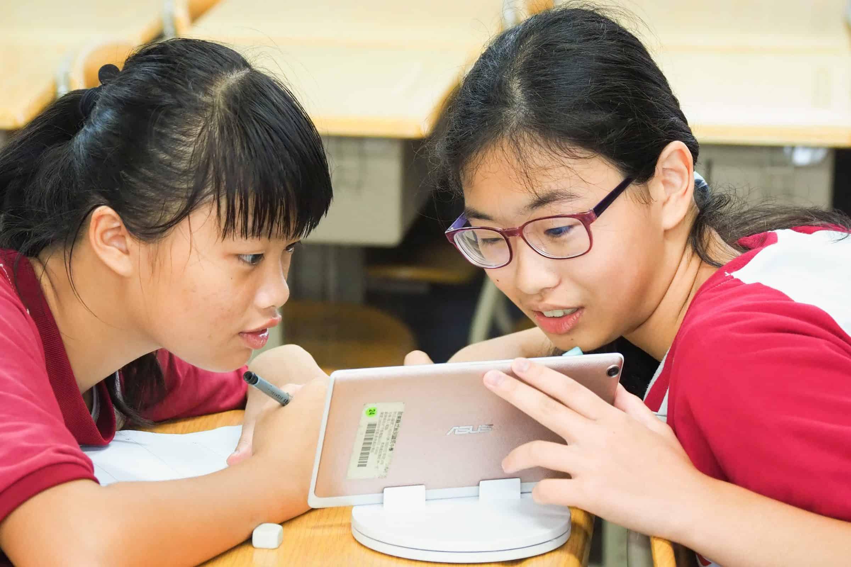 圖為兩個孩子一起使用平版、討論均一教學平台的畫面。透過影片教學的輔助,讓孩子能調整適合自己的步調學習。凸顯出均一透過科技工具,提供孩子符合需求、超越時空限制的「個人化教育」