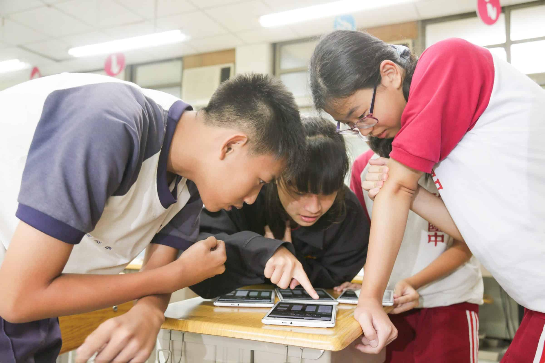 圖為四個孩子圍著桌子,一起操作、討論均一教學平台習題內容的畫面。可以看出他們相當專心與認真。