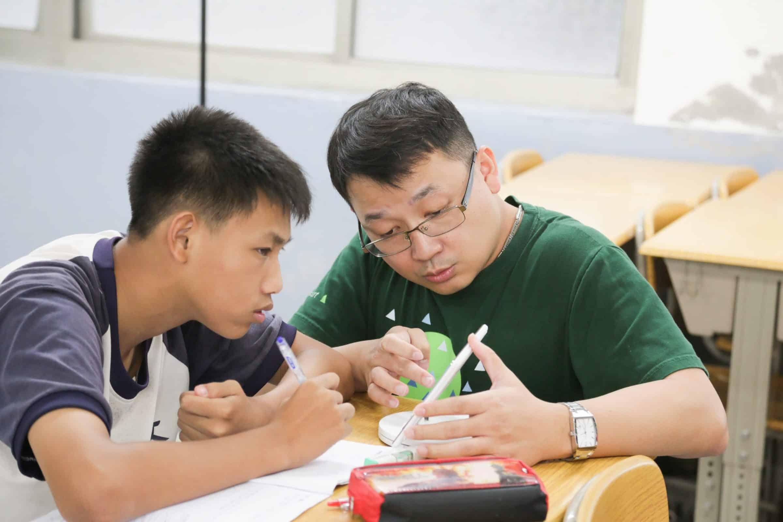 圖為教室內,老師親自在學生旁邊,蹲下身子,教導學生習題的畫面。 透過均一教學平台,讓老師與家長角色進化,透過數據分析即時掌握孩子的學習狀況,省時省力地創造「因材施教」的教育環境,讓老師把時間花在更需要的孩子身上,或教孩子那些更重要的、課本上沒寫的素養知識、品格教育等,真正落實個人化學習。