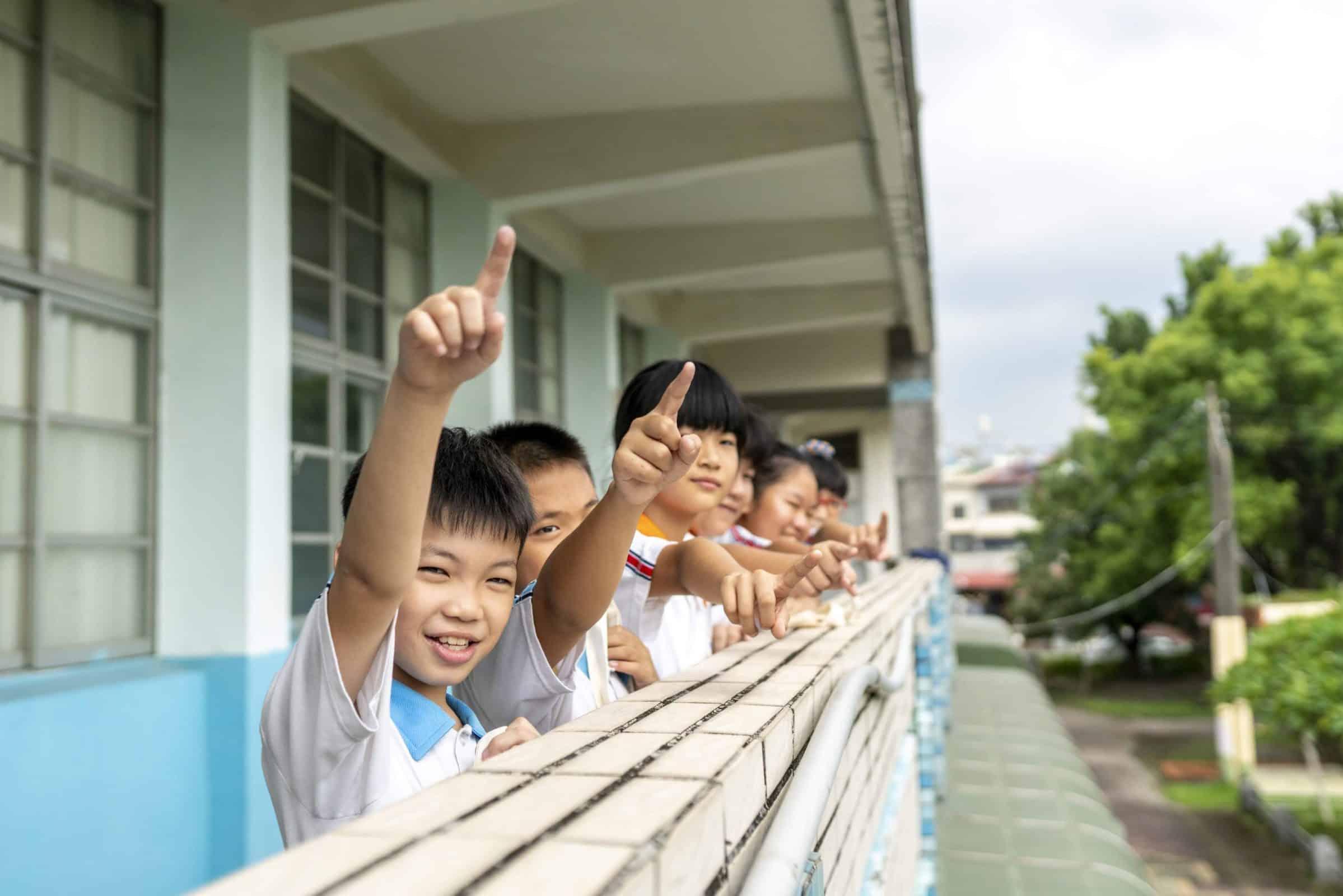 圖為一群可愛的孩子們,手一同比向遠方。 象徵著透過均一,可以點亮孩子們的學習動機,帶領他們在學習這條路上走得更遠、更穩。